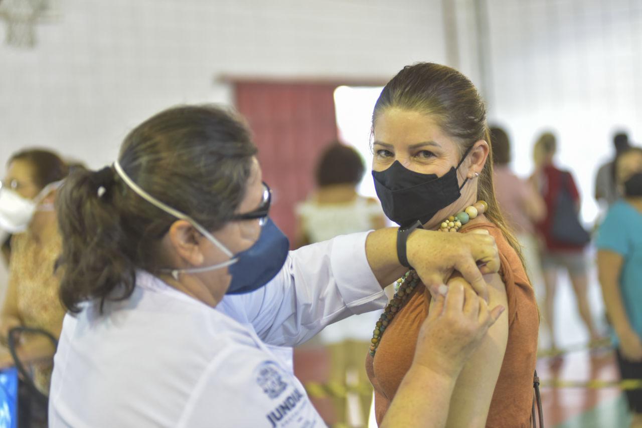 Imagem mostra enfermeira, com máscara azul e jaleco branco, aplicando vacina em mulher com vestido laranja