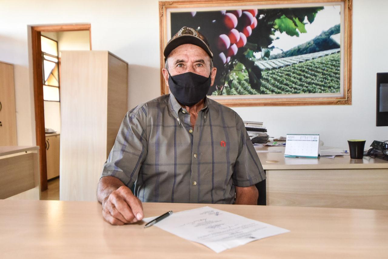 Imagem mostra homem, com boné e máscara, com caneta e papel em cima da mesa.