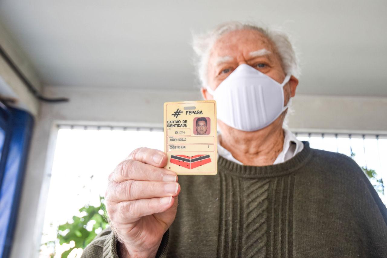 Homem em pé, usando máscara, segura à sua frente um crachá com texto e foto