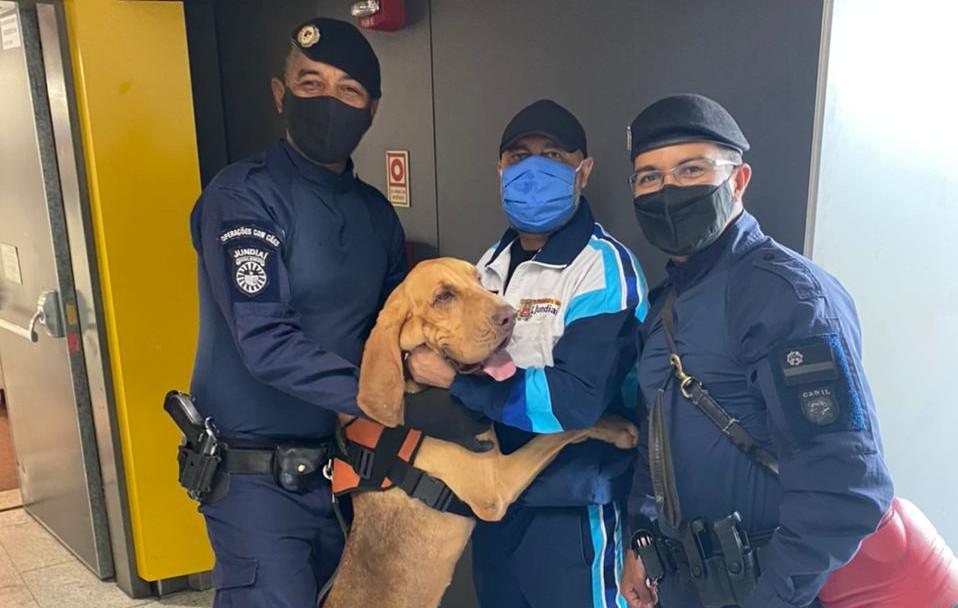 Dois homens fardados e um homem com agasalho esportivo, todos com máscaras , em pé, com um cachorro de grande porte também em pé e apoiado