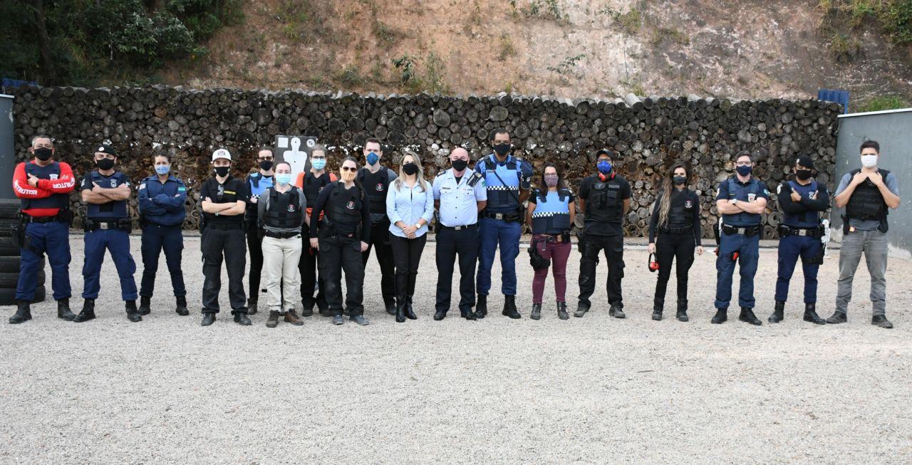 Pessoas usando máscaras perfiladas, algumas com coletes à prova de balas e outras com uniformes policiais, em área descampada