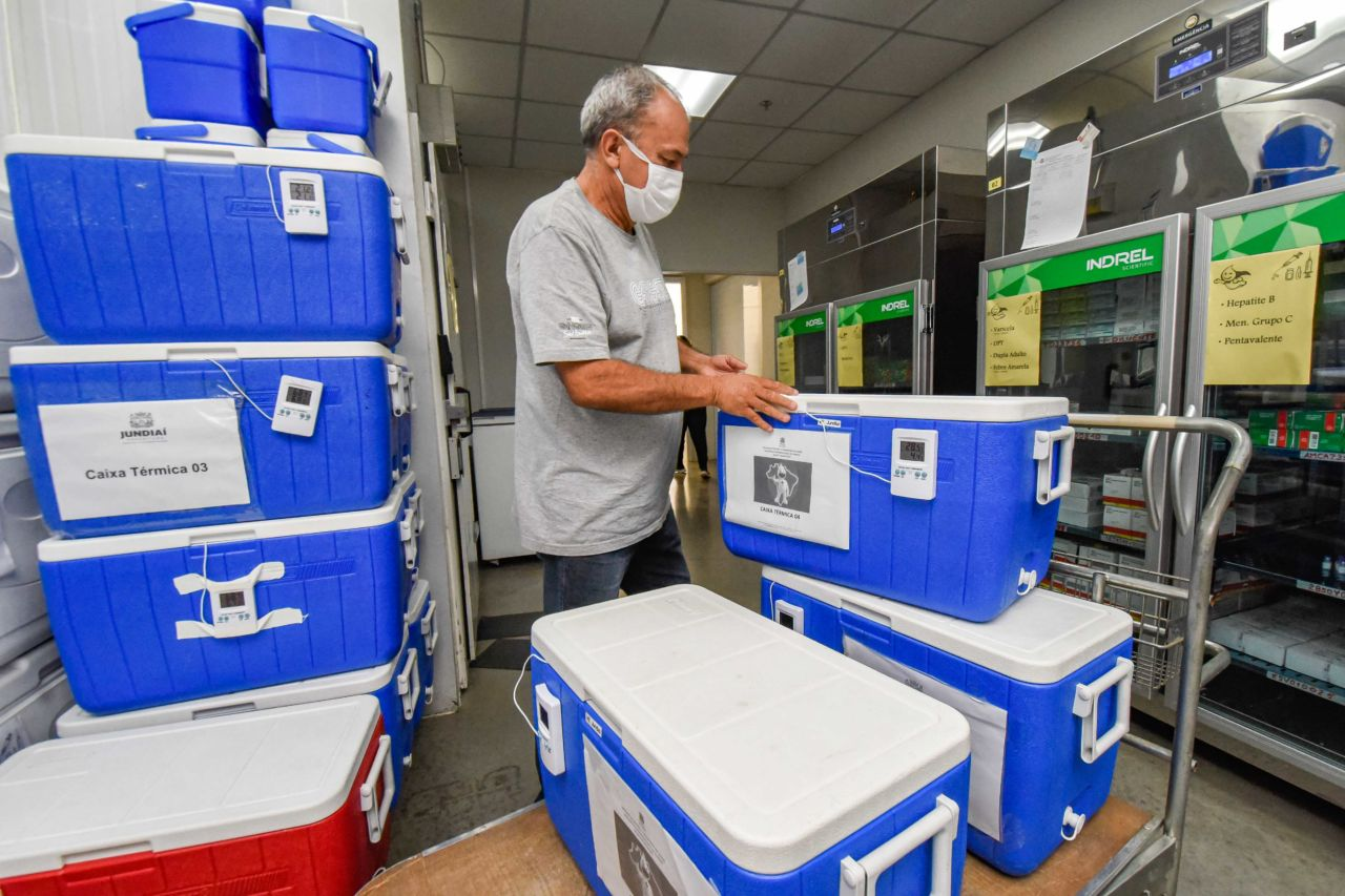 Imagem mostra homem ao lado de carrinho com caixas térmicas azuis, com tampa branca.