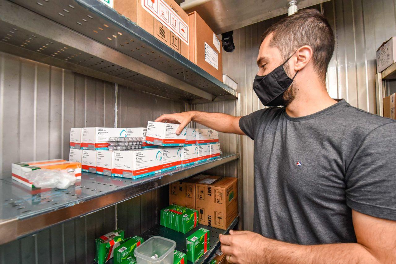 Imagem mostra homem dentro mexendo em caixas da vacina