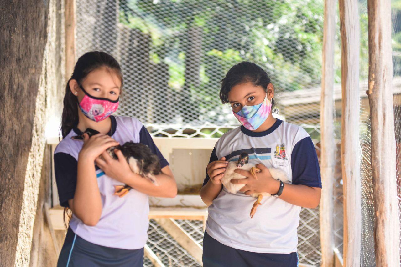 Imagem mostra meninas com  uniforme escolar, máscara. Cada uma segura um pato no colo.