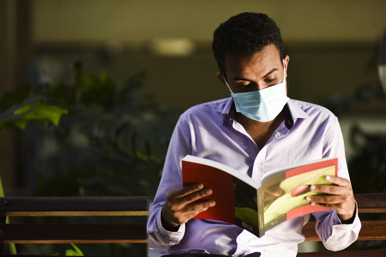 Rapaz de máscara, sentado em banco de praça, segurando e lendo livro, com vegetação ao fundo.