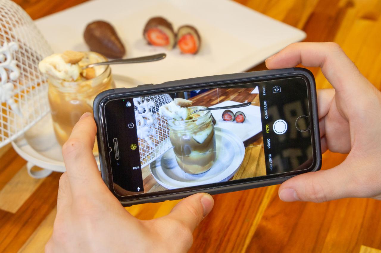 Duas mãos seguram um celular na horizontal fotografando um recipiente de vidro com doce e uma colher e doces com morangos ao fundo