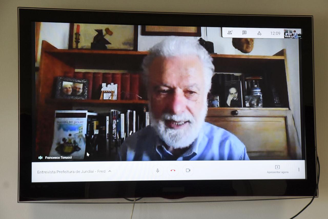 Monitor de televisão com rosto de homem com barba e cabelos brancos, com estante com livros e fotos ao fundo