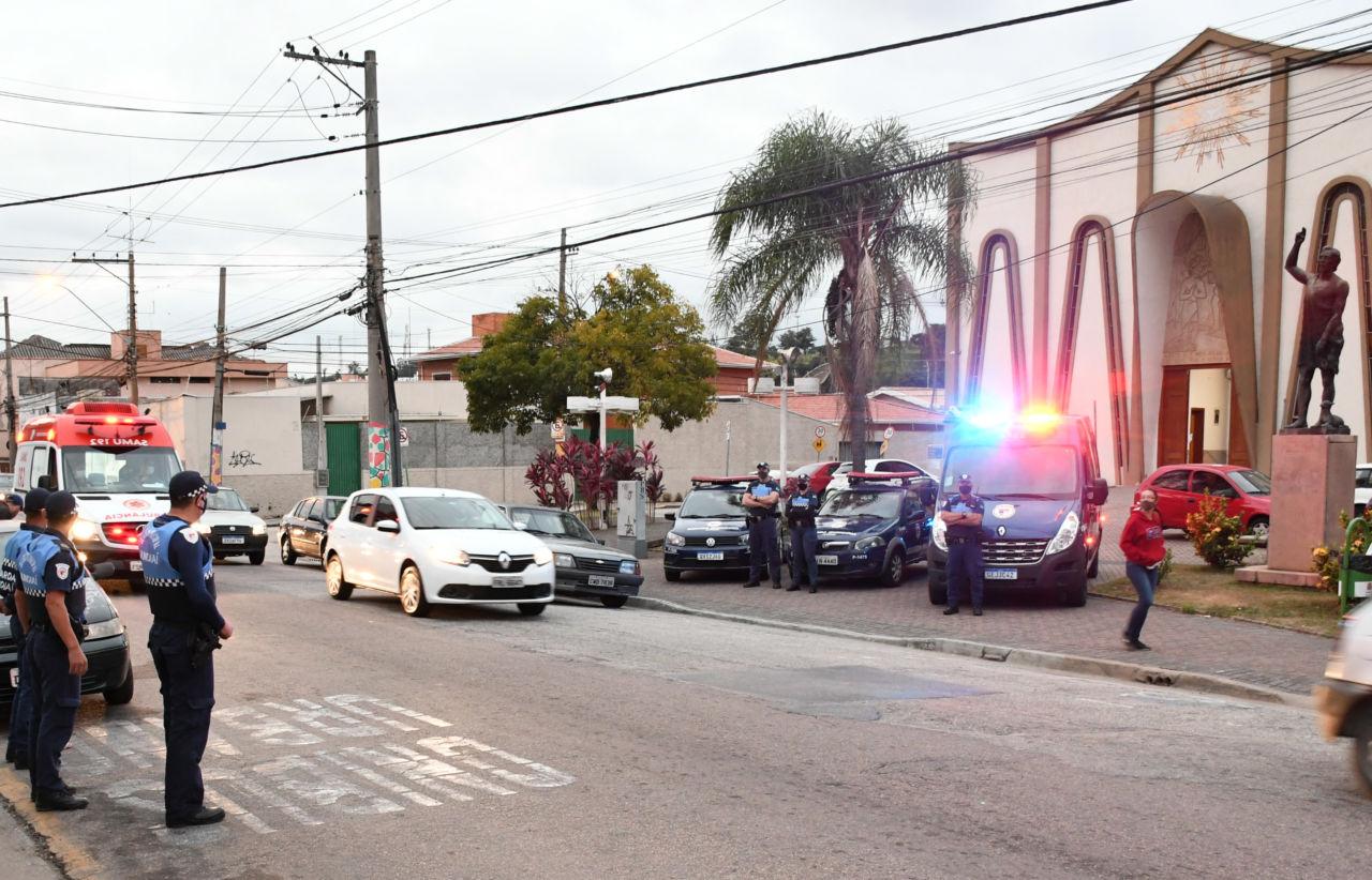 Avenida com fluxo de veículos, com homens fardados em pé sobre o asfalto e viaturas policiais estacionadas sobre a calçada.