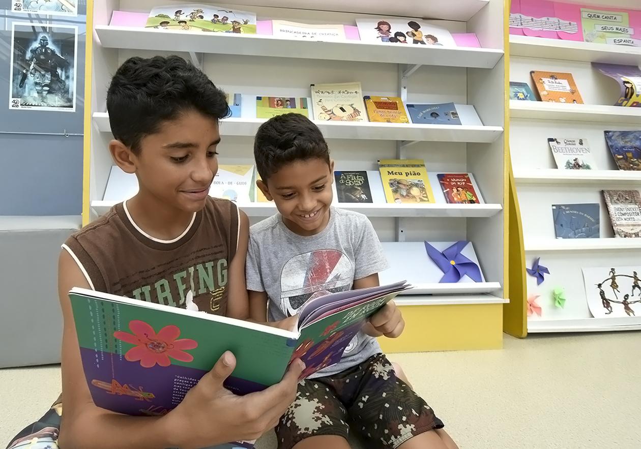 Dois meninos, sentados lado a lado, olham para livro com semblante risonho.