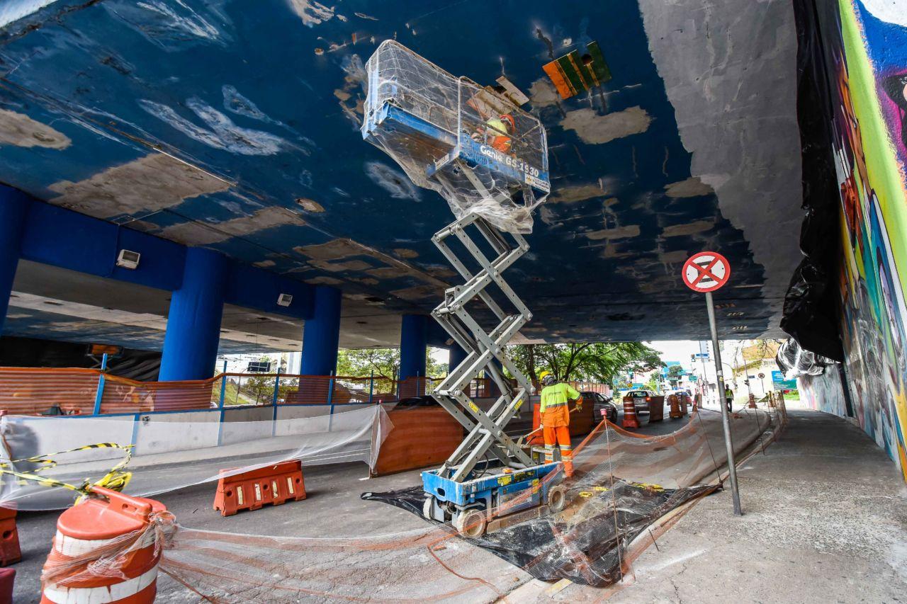 Homem trabalha sobre andaime, embaixo do viaduto Romão Nasser