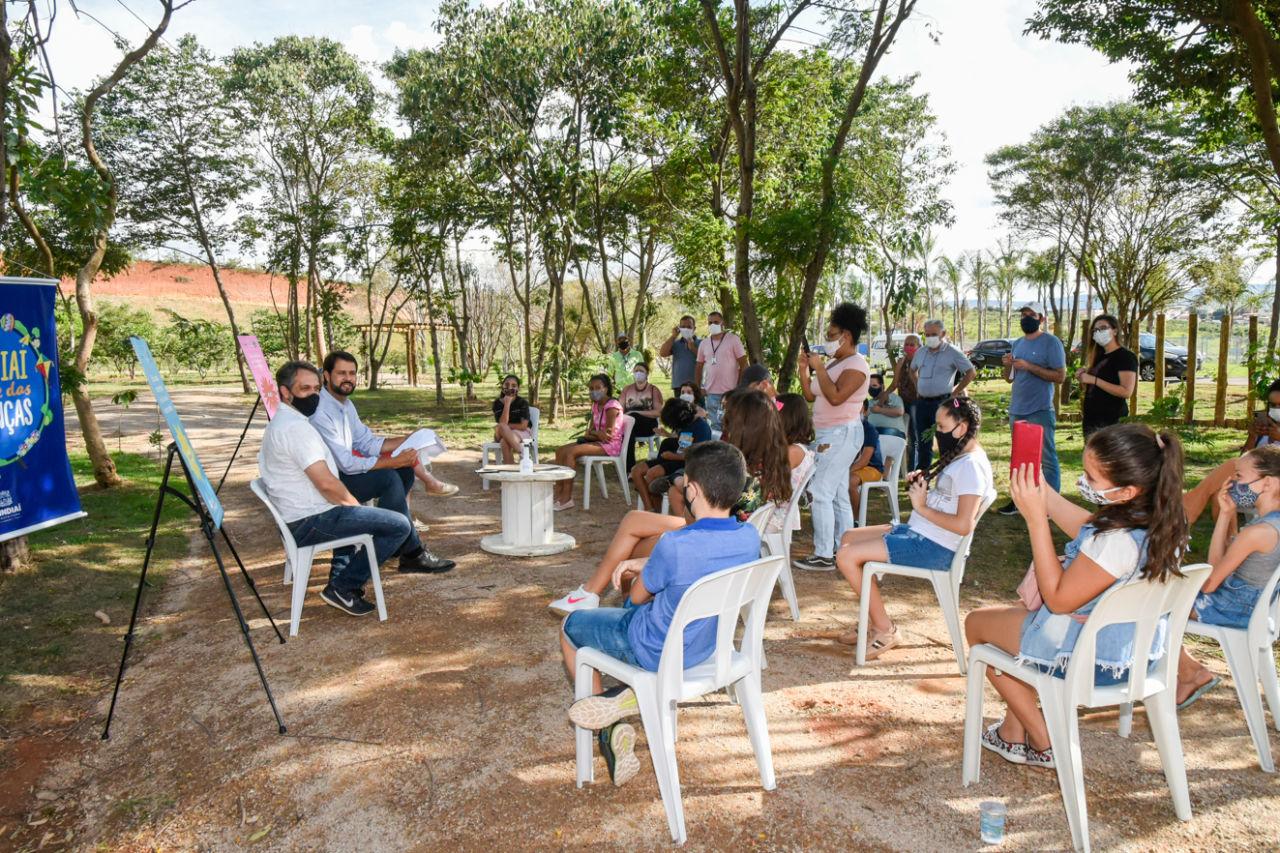 Grupo de adultos e crianças sentados sob a sombra de árvores, conversando como que em reunião