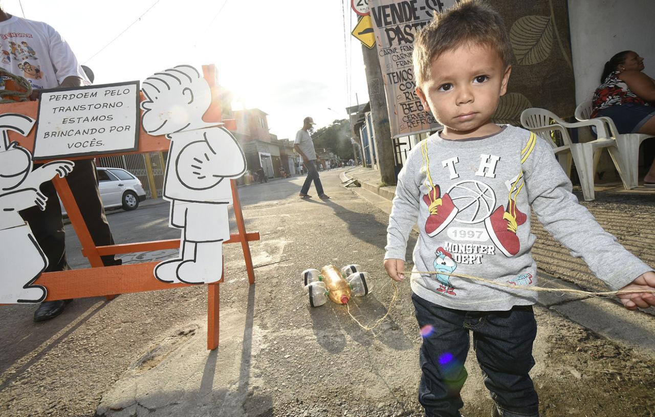 """Criança com blusa estampada e calças, em pé, segurando uma corda puxando brinquedos com garrafas plásticas ao lado de cavalete com desenho e dizeres: """"Perdoem pelo transtorno. Estamos brincando por vocês""""."""