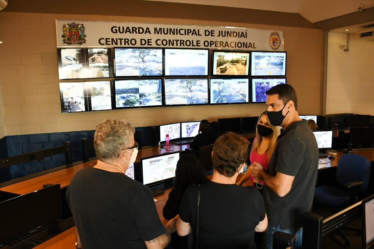 Pessoas em pé e usando máscaras conversando, em sala com computadores e telas afixadas em parede ao fundo com imagens de monitoramento de câmera