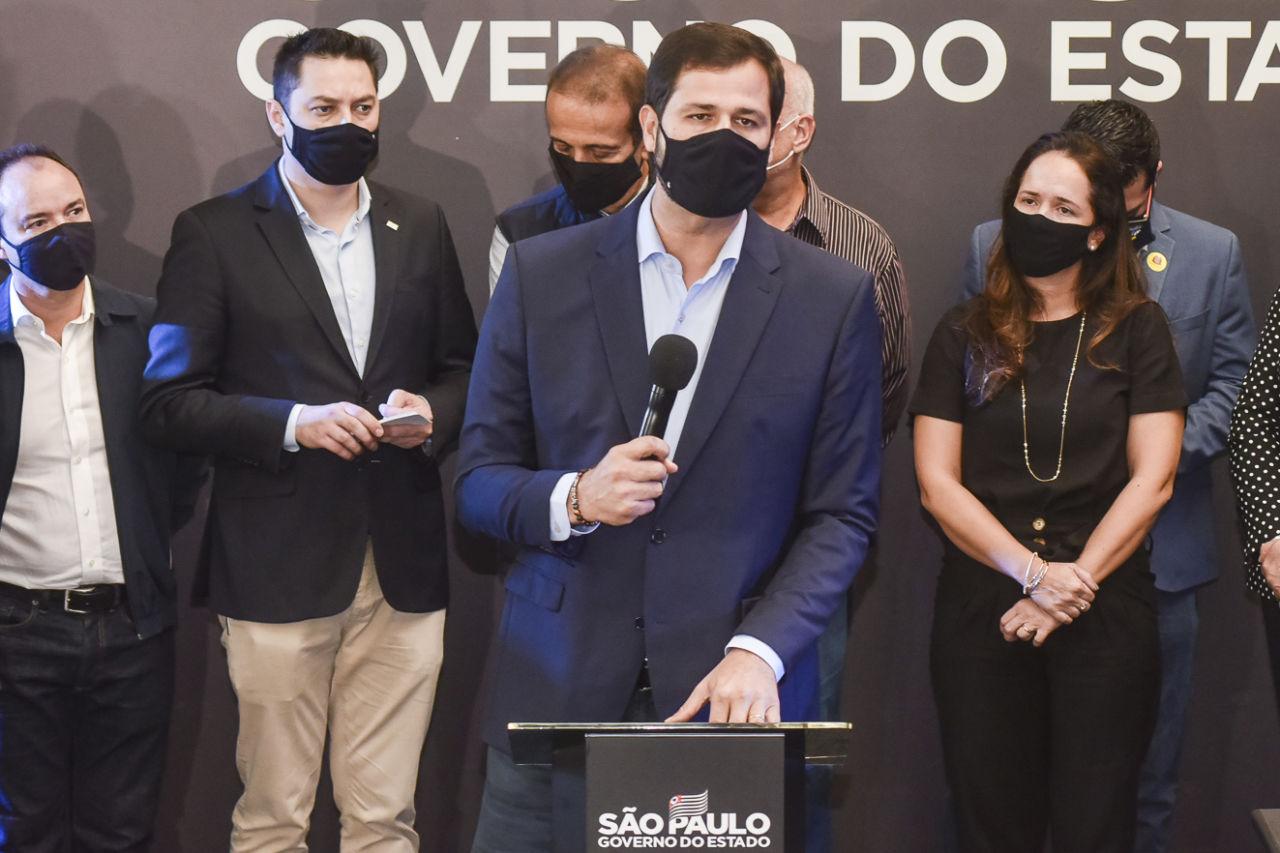 Imagem mostra homem, de terno azul, segurando microfone. Há pessoas no fundo.