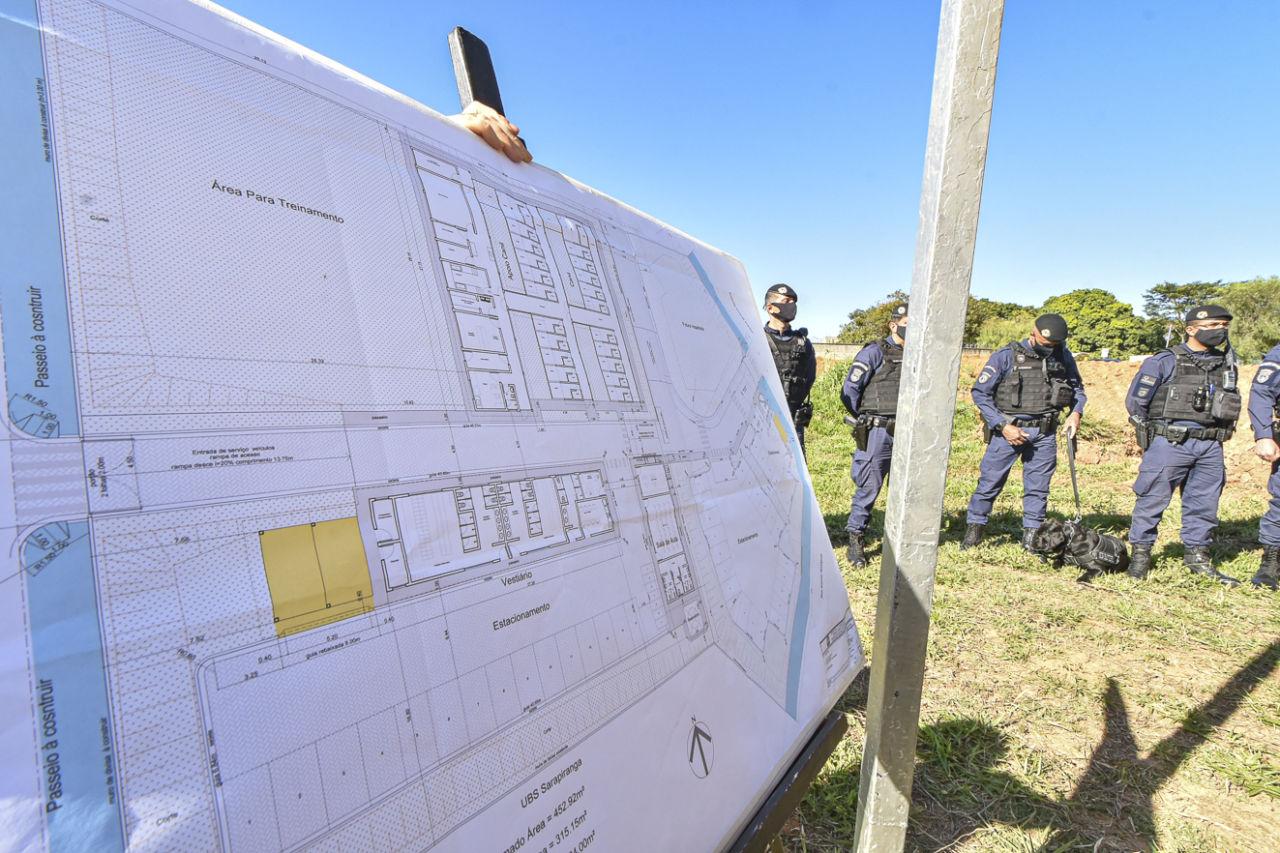 Imagem mostra projeto no foco, ao fundo, guardas municipais e cachorro