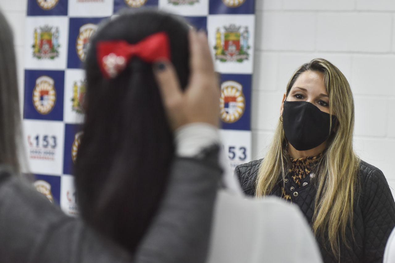 Mulher de máscara e cabelos longos olha para silhuetas embaçadas de duas mulheres também de cabelos longos, uma com um laço na cabeça, que é amparada por mão