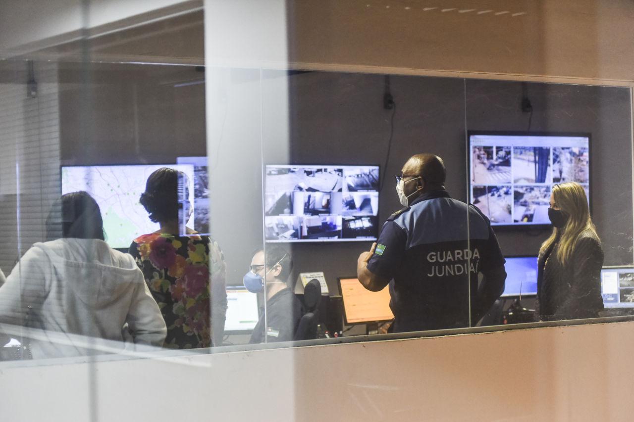 Pessoas usando máscaras em sala de vidro, com telas de videomonitoramento na parede