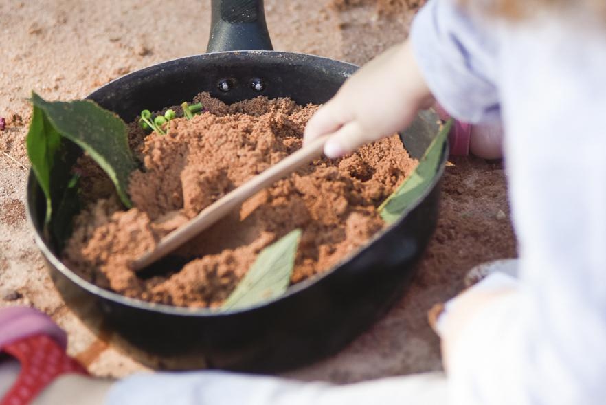 criança brinca com panela de ferro, com areia e plantas dentro.