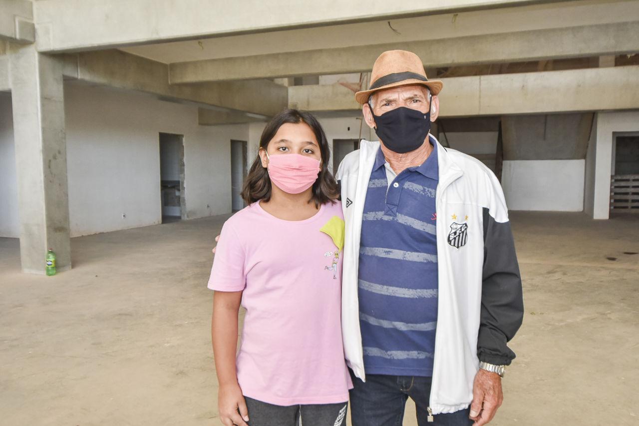 Imagem mostra menina com homem idoso ao lado, em espaço em construção