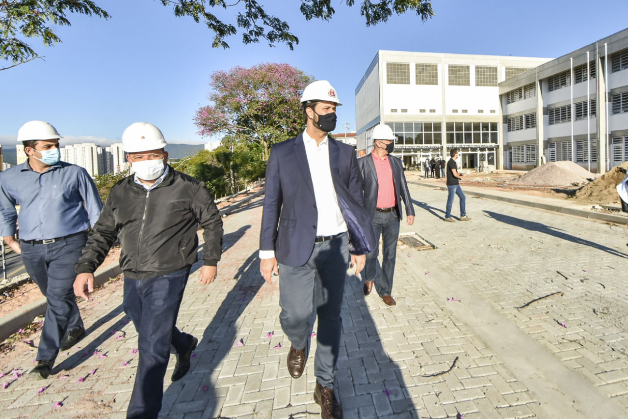 Imagem mostra quatro homens caminhando, com prédio ao fundo.