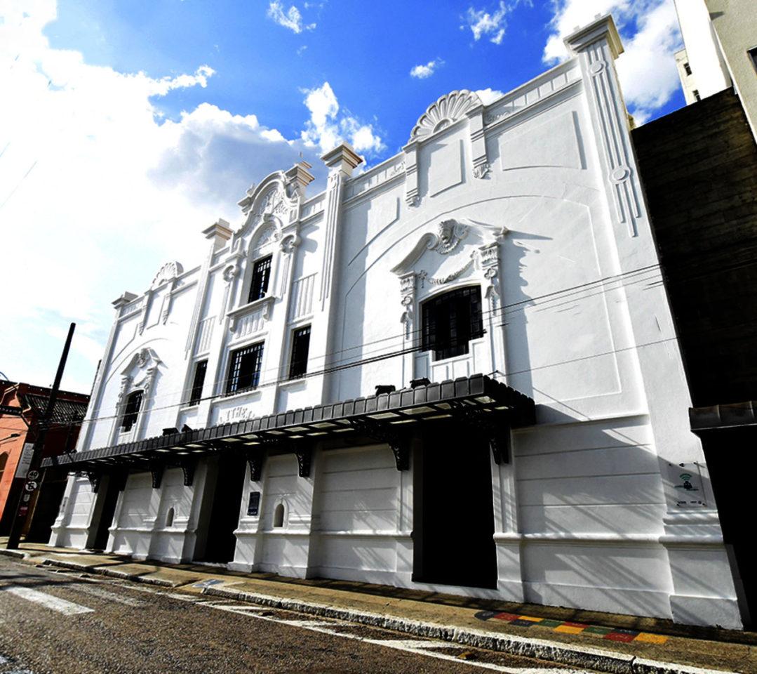 imagem mostra o centenário Teatro Polytheama. Construção com pintura branca, adornos nas paredes e portas e janelas pintadas de preto.