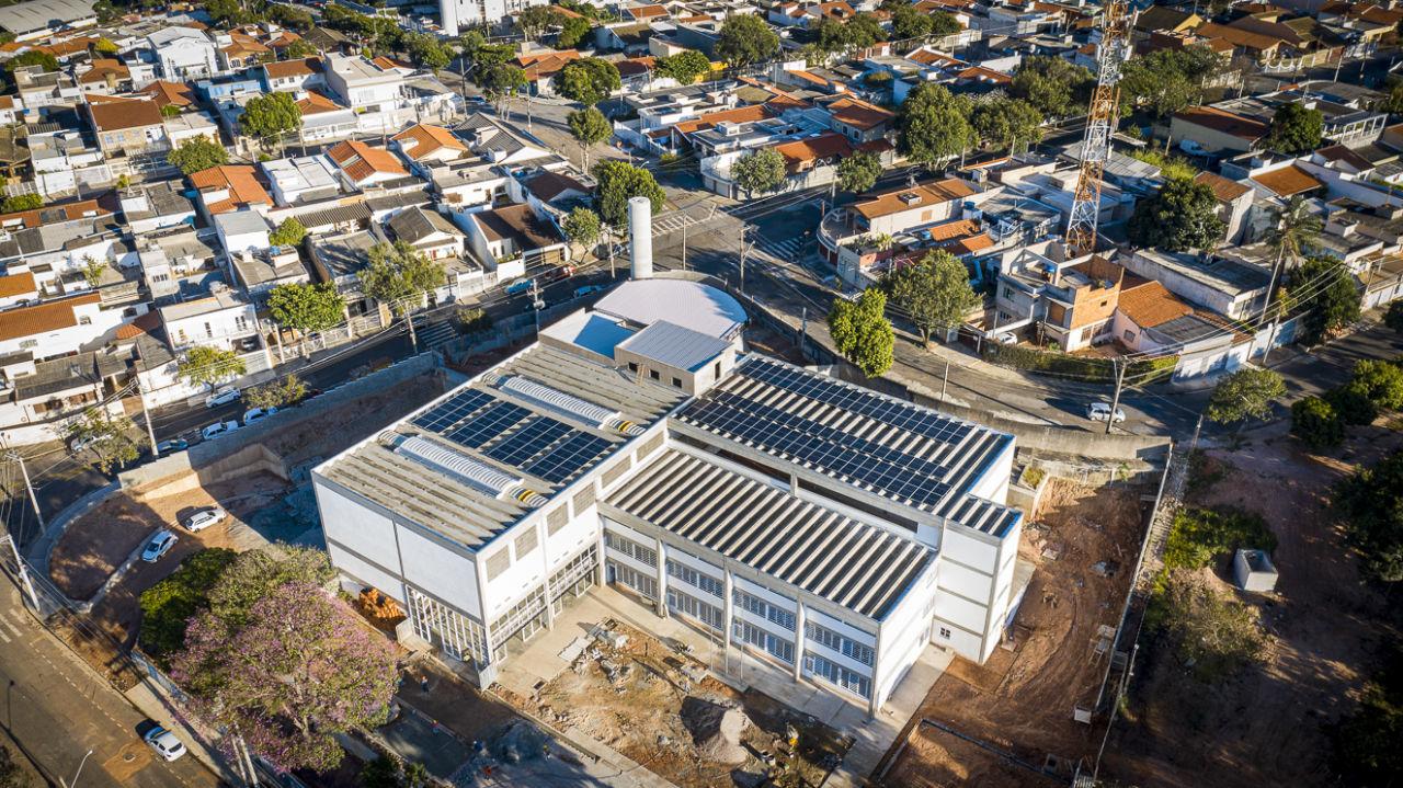Imagem mostra prédio, com obras no entorno.  No telhado há diversas placas azuis que são para a geração de energia fotovoltaica.