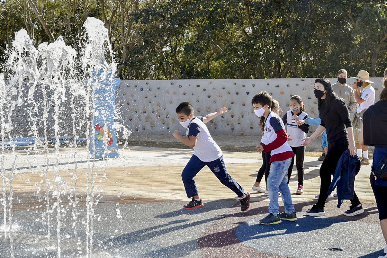 Imagem mostra crianças correndo em direção de fonte de água
