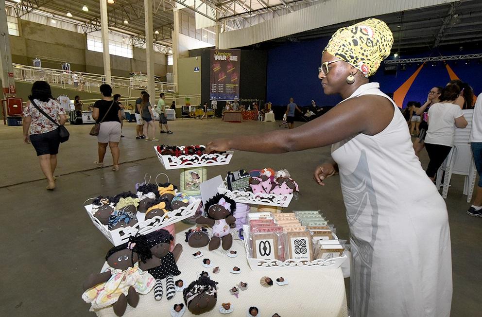 Mulher negra com turbante, mexendo em bonecas de artesanato sobre mesa, em galpão com pessoas transitando