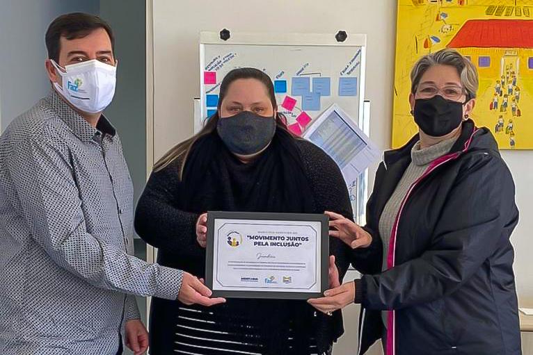 """imagem mostra homem e duas mulheres com certificado """"Movimento Juntos pela Inclusão"""" nas mãos.  Todos estão usando máscara facial"""