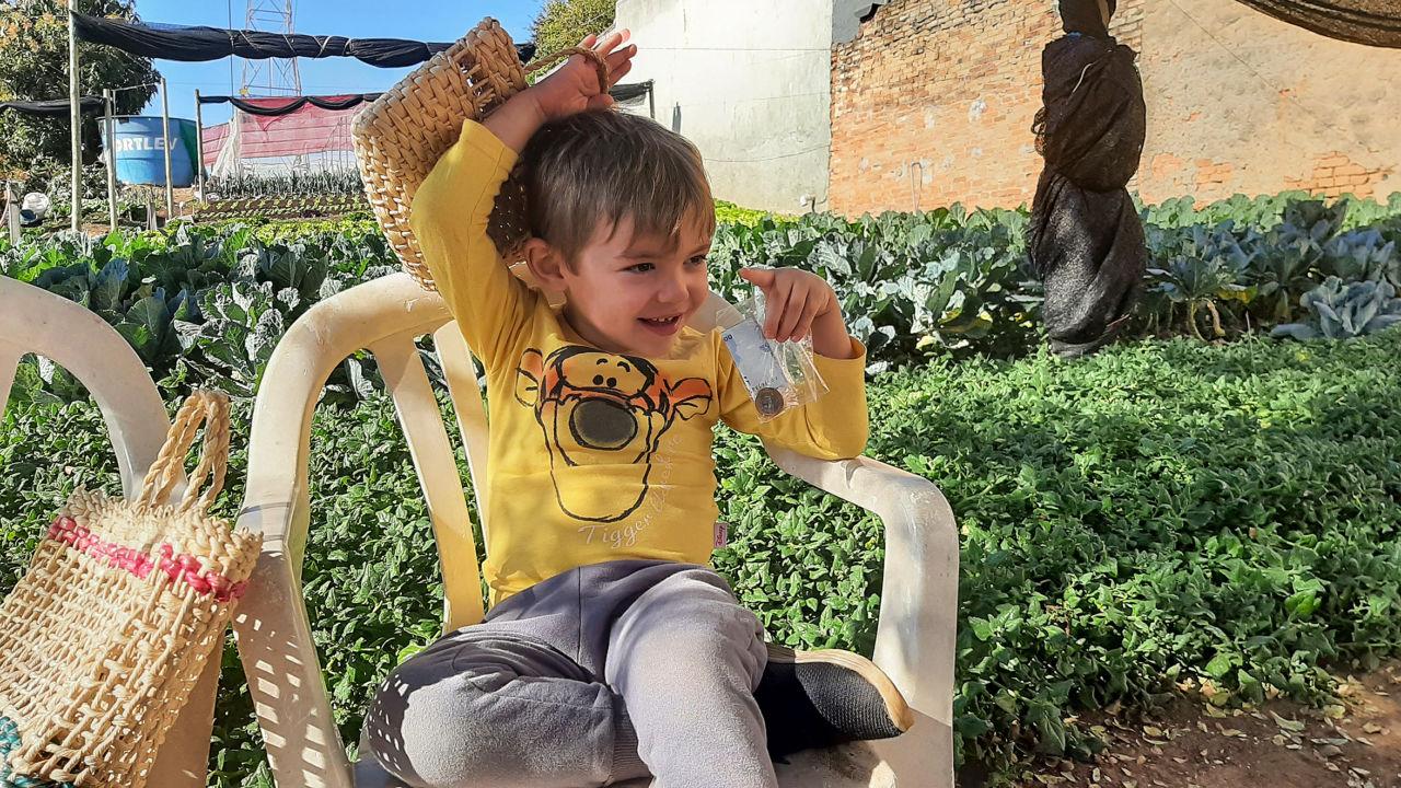 imagem mostra criança, com camiseta amarela, calça cinza, ele está sentando em frente a uma horta e segura uma sacola de palha em uma das mãos e na outra um saquinho com moeda e dinheiro