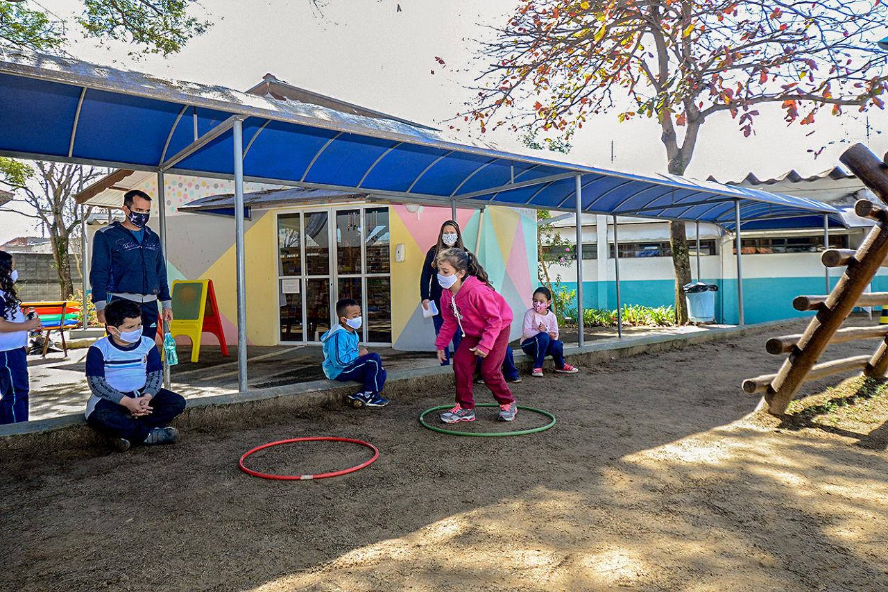 em um parquinho de areia há bambolês  coloridos no chão, menina, com roupa rosa, pula de um para outro. há crianças sentadas em mureta e assistem à atividade