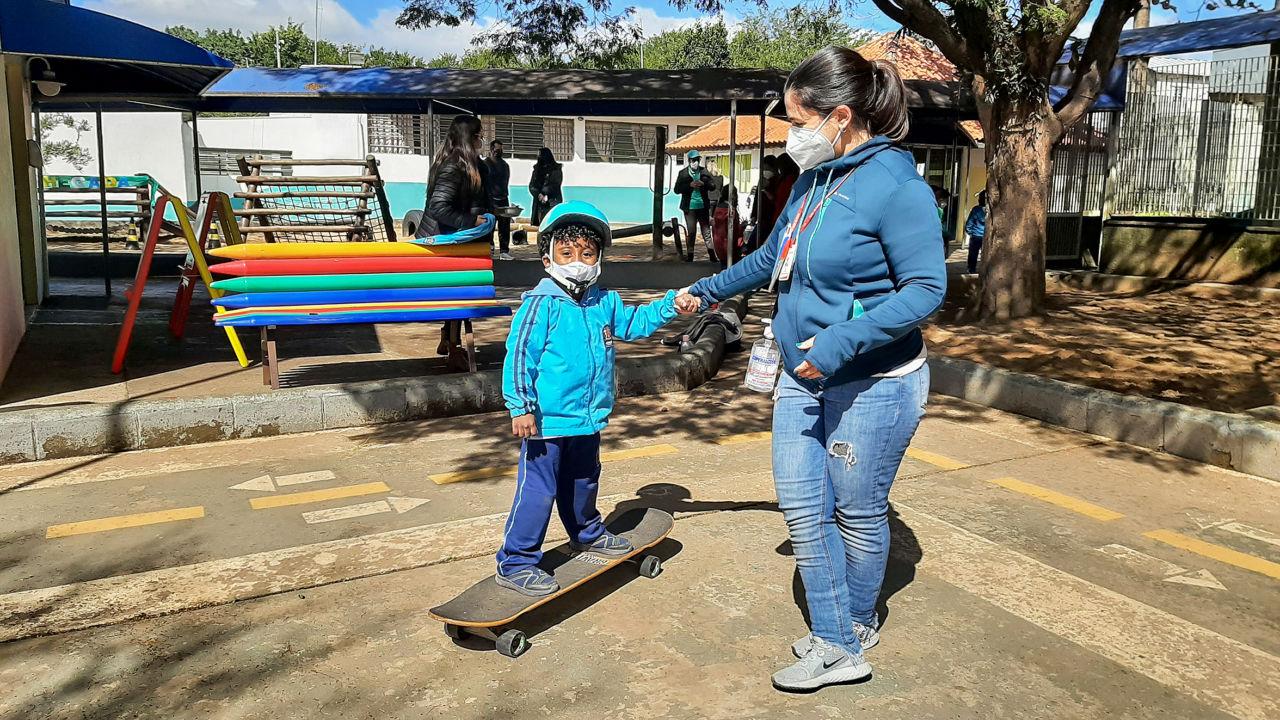 De unforme azul, garoto está usando capacete de segurança, em cima de skate, de mãos dadas com professora que está em pé, usando máscara e com frasco de álcool em gel na cintura