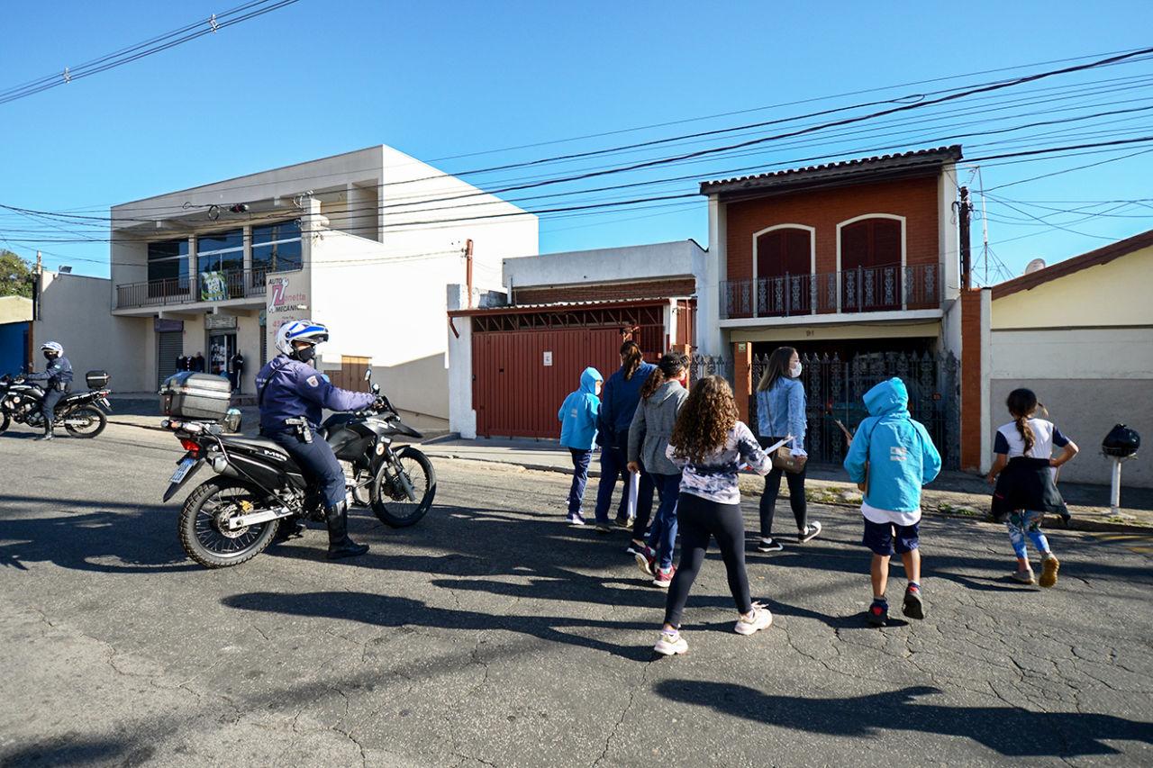 Imagem mostra crianças atravessando a rua, juntamente com adultos (professores). Duas motos da Guarda Municipal de Jundiaí fazem a segurança.
