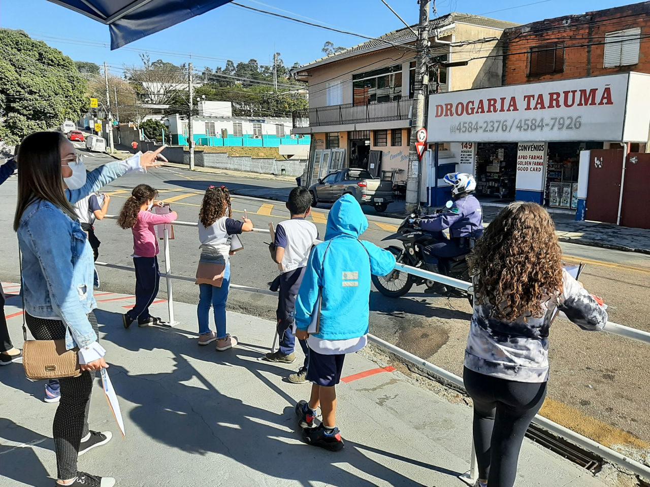 Mulher loira, aponta para comércio em que está escrito Drogaria Tarumã. Junto dela estão crianças que olham com atenção para o escrito.  Ao fundo, moto da guarda municipal de Jundiaí, vestido com farda azul.