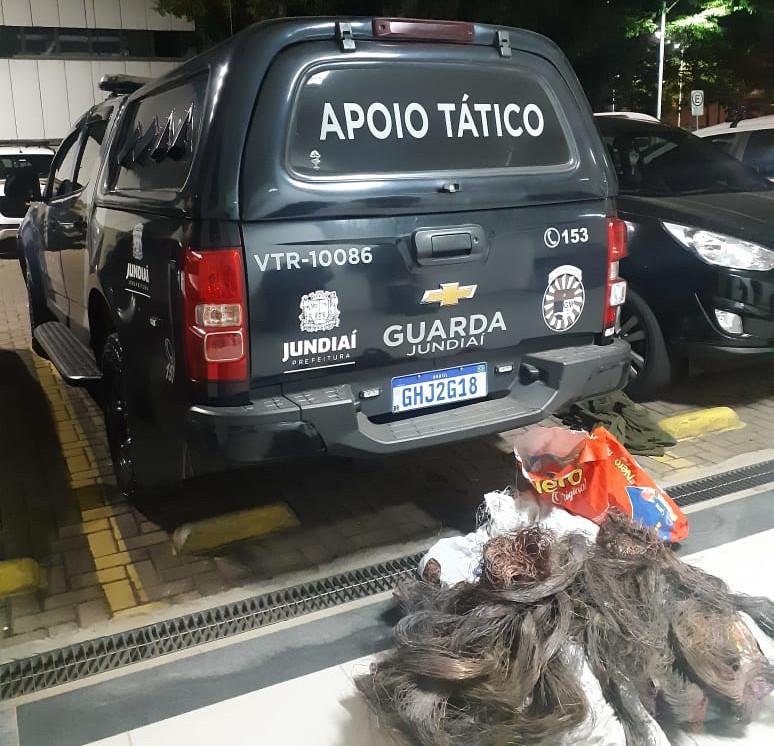 Traseira de veículo policial com emaranhado de fios com sacolas sobre o chão