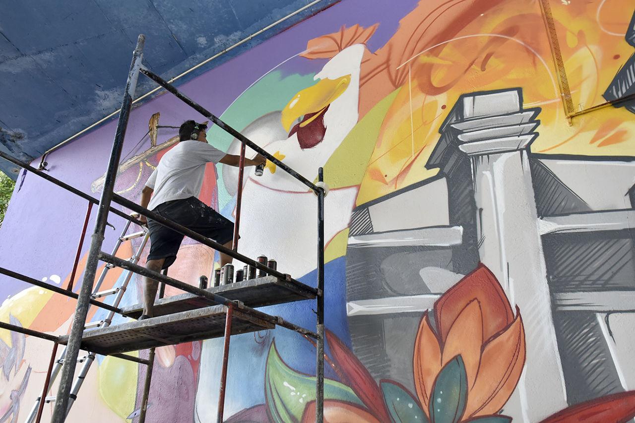 Homem de bermuda e camiseta com fone de ouvido sobre andaime, fazendo pintura com tubos de spray em parede