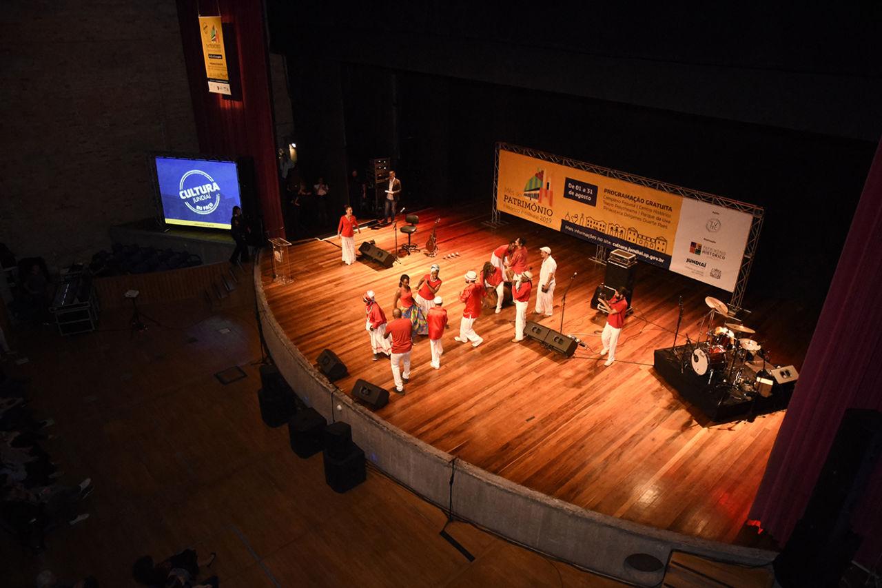 Foto do alto de palco iluminado, com pessoas em performance de música e dança