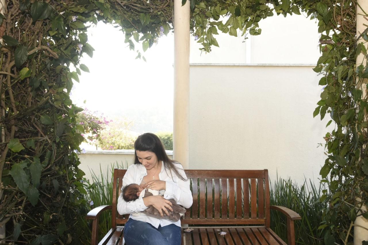 Mulher amamenta bebê, sentada em banco de madeira sob pergolado com folhagens