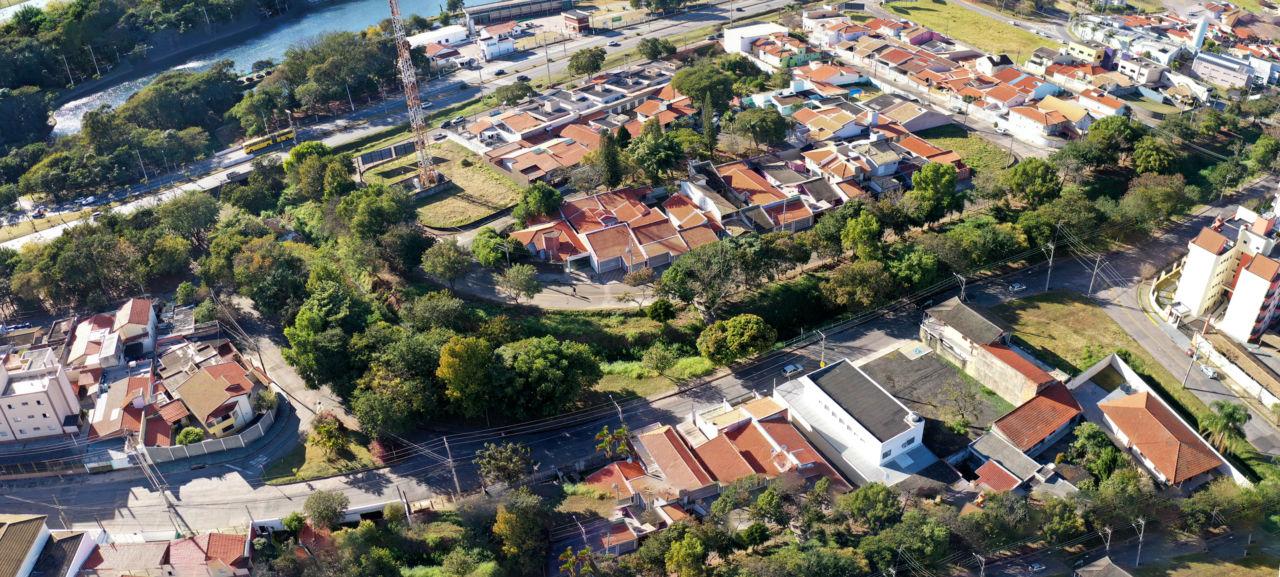 Imagem aérea com casas e construções, rodeadas por muitas árvores