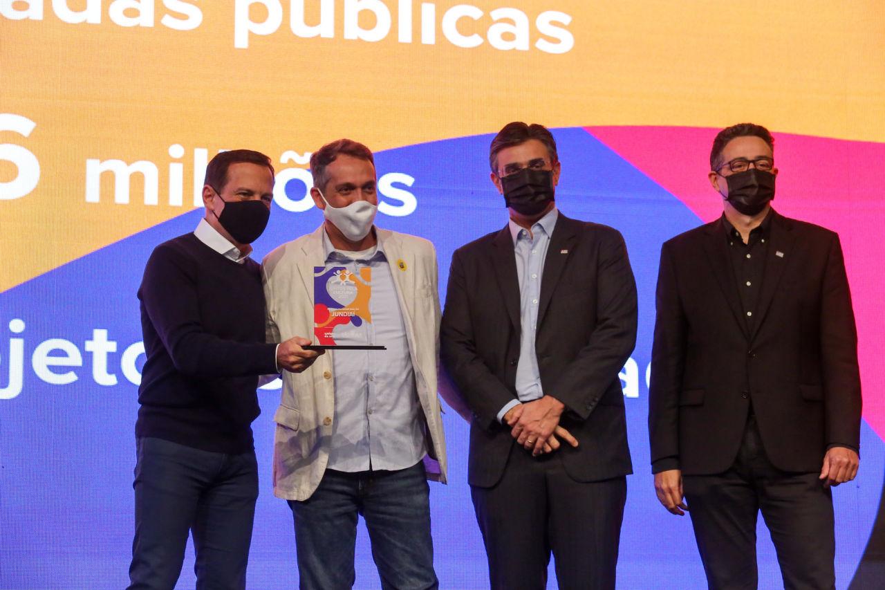 Quatro homens de máscara um ao lado do outro, dois deles segurando um troféu, com fundo colorido