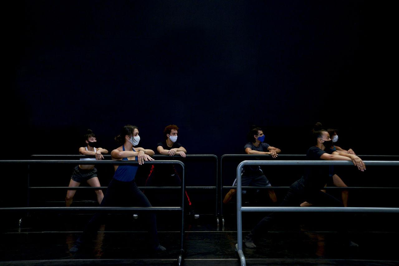 Pessoas dançando no entorno de barras, com palco, com pano escuro ao fundo