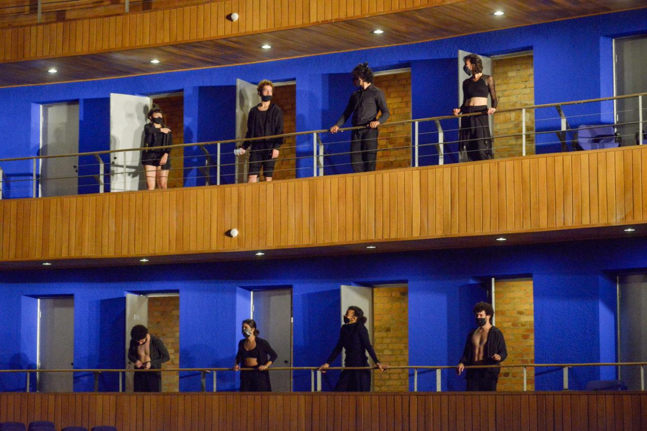 Oito bailarinos de roupas pretas e máscaras se apresentam em balcão de teatro