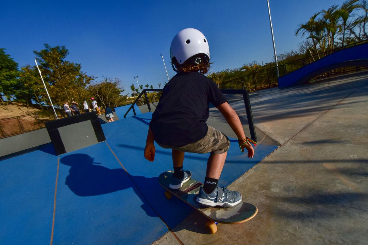 Criança de tênis, bermuda, camiseta e capacete, de costas, anda de skate em pista