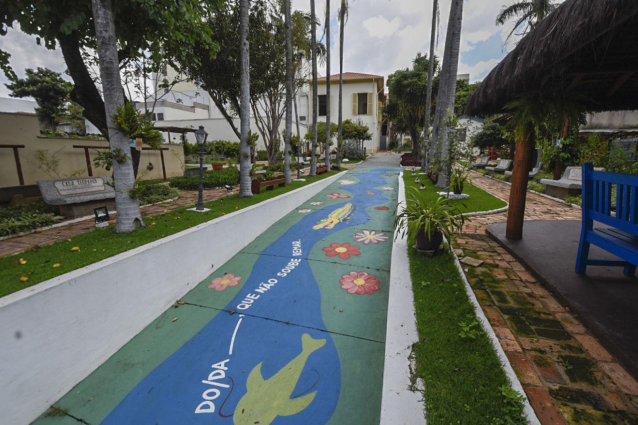 Jardim com árvores e flores, com pintura de solo que lembra um rio