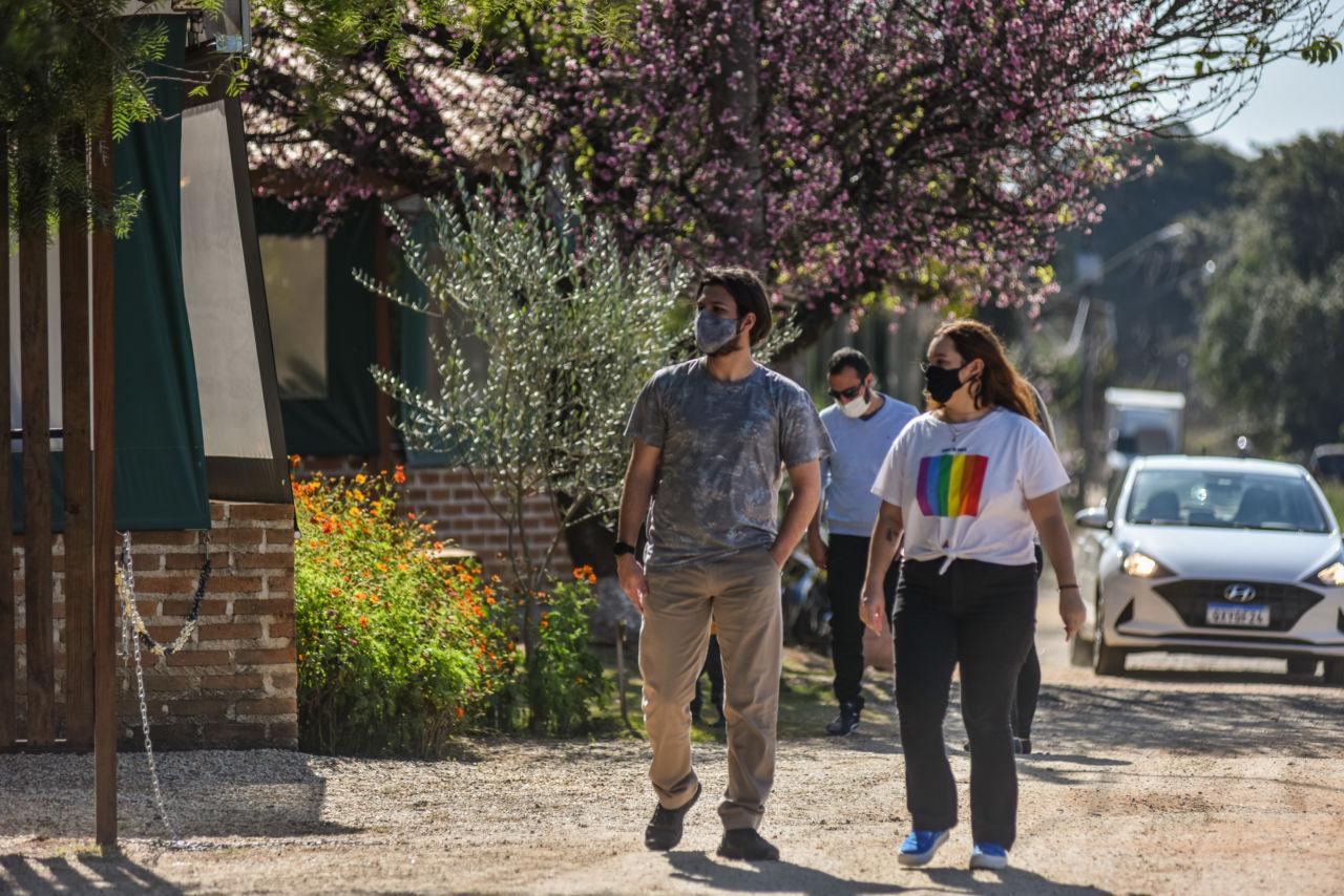 Pessoas de máscara caminhando sobre estrada de terra, com carros, casas e vegetação ao fudndo