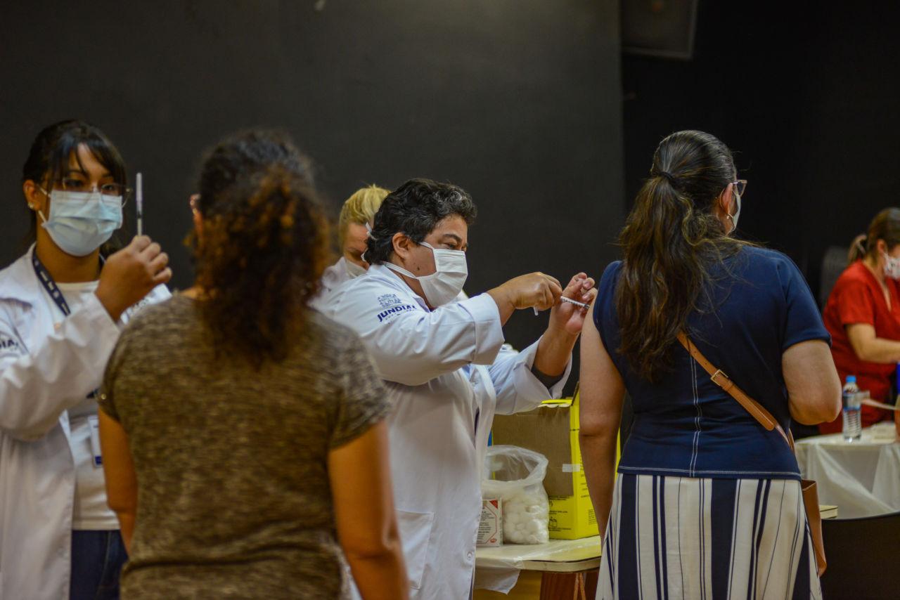 Profissionais de saúde, com máscaras e jalecos, aplicando vacinas em pessoas em fila