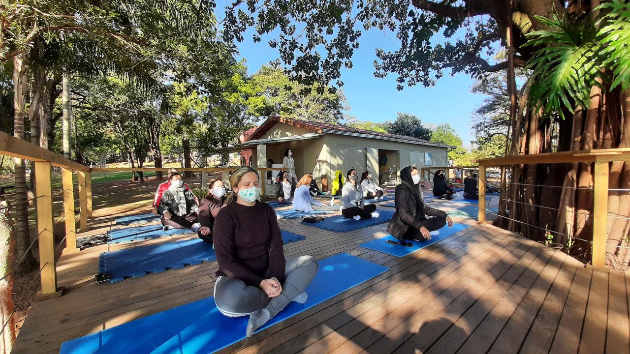 em um deck de madeira, pessoas estão sentadas em tatames, praticando meditação
