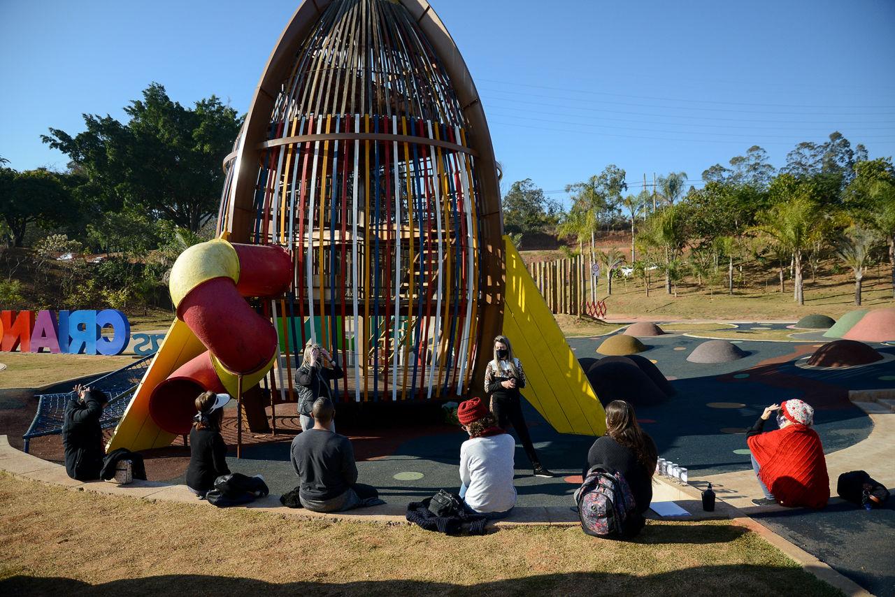 ao fundo foguete de madeira do Mundo das Crianças. Educadores sentados no entorno