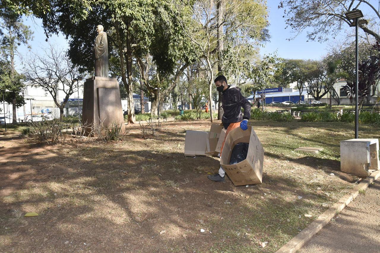 Homem com máscara e luvas carrega caixas de papelão em praça onde de se vê estátua de formato humano