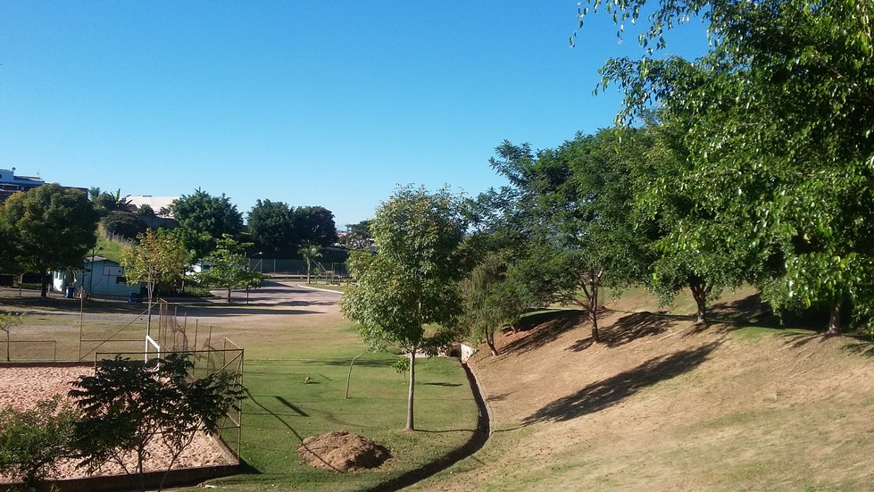 parque com gramado. À esquerda quadra de areia, ao fundo construção com parede azul clara, à direita árvores